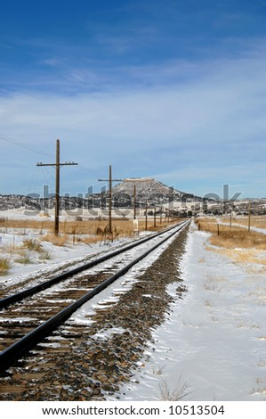 Railroad track disappears into the distance.  Winter scene with snow on tracks.  Mesa looms in distance.  Blue skies. - stock photo