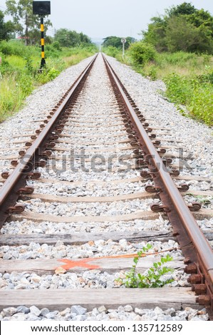 Railroad track into the distance and side of the grass - stock photo