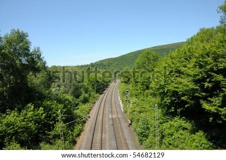 Railroad track running through a green landscape - stock photo