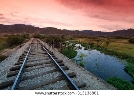 Railroad track with sunrise sky and a river, Utah, USA. - stock photo