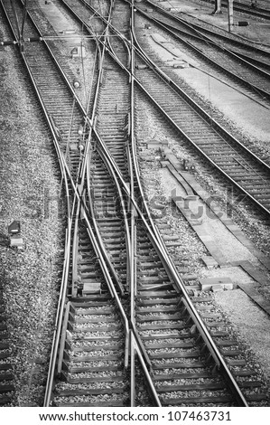 Railroad tracks and switches in a switching yard in black and white showing three parallel tracks with a set of tracks crossing all of them and the switches to control traffic.