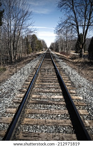 Railroad tracks converging in the distance - stock photo