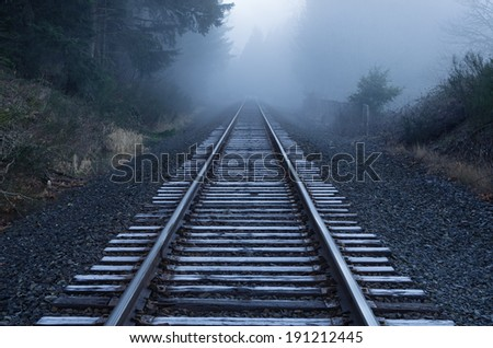 railroad tracks fade into the fog on a frosty Oregon morning - stock photo