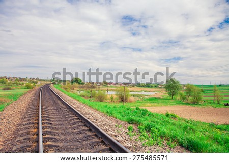 railroad tracks going into the distance in the summer - stock photo