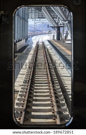 Railroad tracks in the winter, viewed from the train - stock photo
