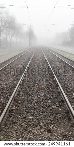 Railroad tracks leading into thick mysterious fog on a cold and wet winter day