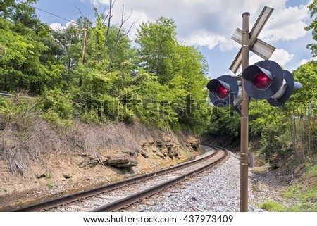 Railroad tracks round a curve with a crossing signal in rural West Virginia. - stock photo
