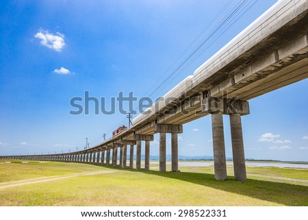 Railroad tracks with freight train passing the reservoir, Pa Sak Jolasid Dam, Lopburi Thailand. - stock photo