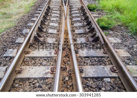 railroad tracks with railroad switch, two paths come together