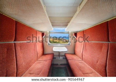 Railroad train interior. Inside of train - red seats; table and window - stock photo