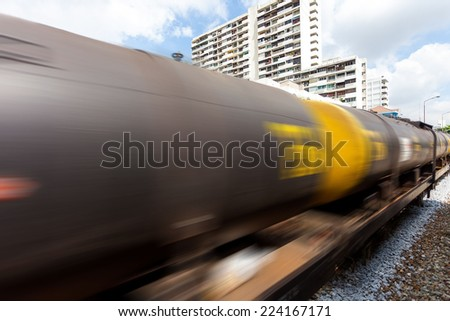 Railroad train of tanker cars transporting crude oil on the tracks with motion blur effect - stock photo
