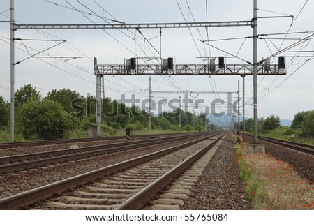 Railroad with signal lights and wires - stock photo