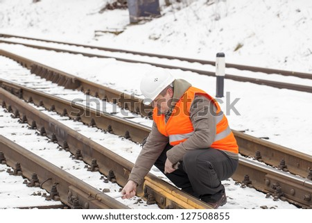 Railroad worker with adjustable wrench on the railroad - stock photo