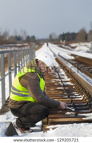 Railroad worker with wrench on the railway bridge - stock photo