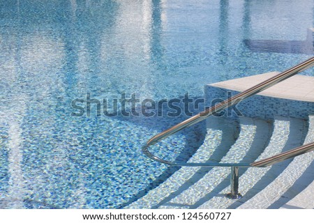 Rails and stairs leading into a blue swimmingpool