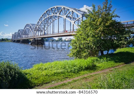Railway bridge over the Daugava river in Riga, Latvia, on a sunny day - stock photo