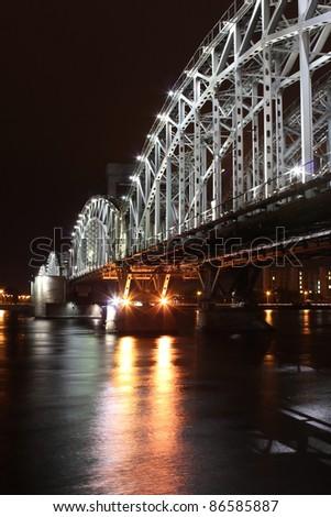 Railway Bridge over the river in the night illumination (Russia, Saint-Petersburg) - stock photo