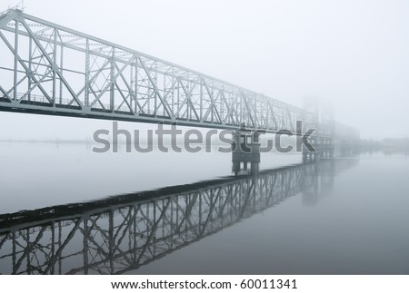 railway bridge through the river.matutinal mist