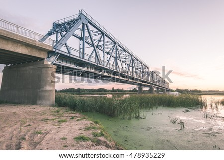 railway bridge with metal rails near river in sunset - vintage film effect