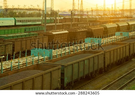 Railway cargo cars carrying coal and logs - stock photo
