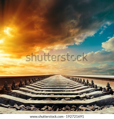 railway closeup to horizon under colored sky in sunset - stock photo
