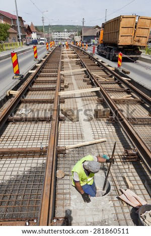 railway construction worker in a hole in the street with traffic - stock photo