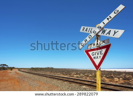 Railway crossing sign next to a long bend in the track. - stock photo