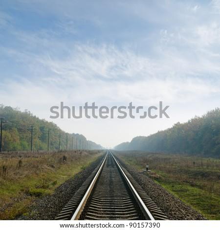 railway goes to horizon in fog - stock photo