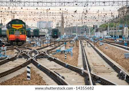 Railway junction. Perspective of crossing rails, traffic lights and train. - stock photo