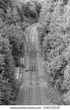 Railway lines running through a wooded area - stock photo