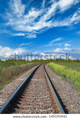 Railway perspective with green grass and blue cloudy sky
