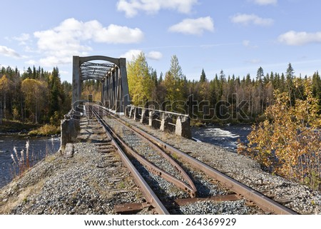 Railway, railroad bridge crosses a river up North. Colorful and sunny day in September. - stock photo