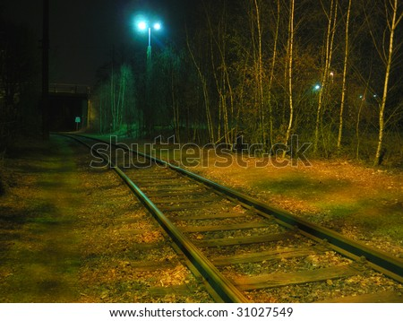 Railway / railroad tracks leading into the black tunnel - Shadow and light - stock photo