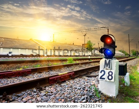 Railway semaphore near industrial station at sunset - stock photo