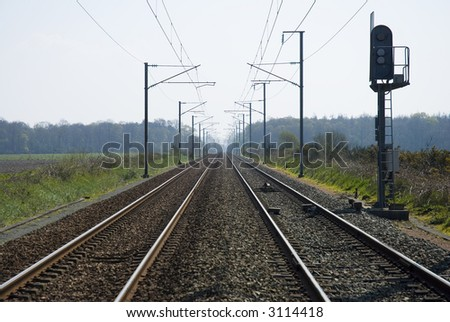 Railway shot with overhear cables and side lights. Centered vanishing point perspective - stock photo