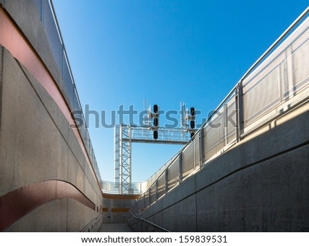 Railway signals at the end of a railway passenger platform and ramp with a blue sky - stock photo