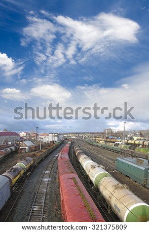 Railway station. Cargo transportation of goods by rail. Train with storage tank. Blue sky and white clouds - stock photo