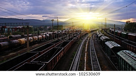 railway station, different trains and wagons at sunset with dramatic sky - stock photo