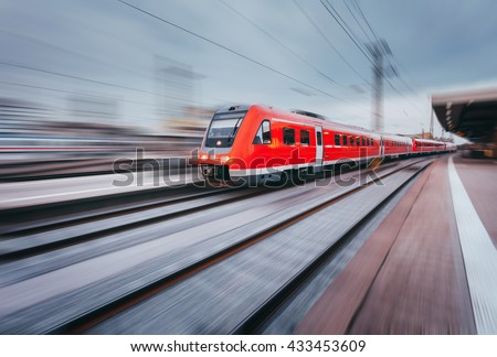 Railway station with modern high speed red passenger train at sunset in Nuremberg, Germany. Railroad with motion blur effect vintage toning. Industrial landscape - stock photo