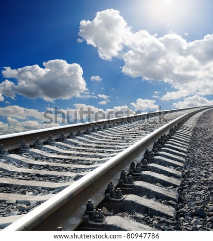 railway to horizon under cloudy sky with sun - stock photo
