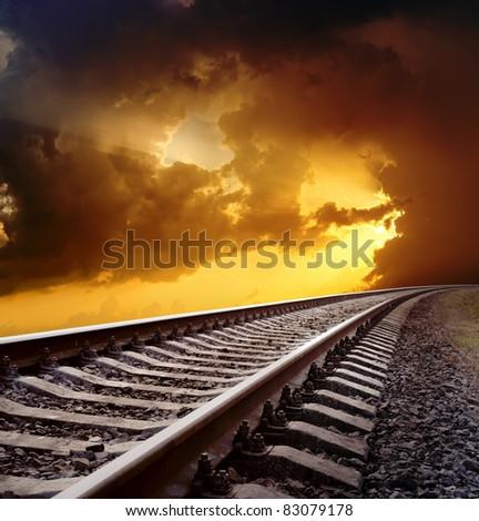 railway to horizon under dramatic sky - stock photo