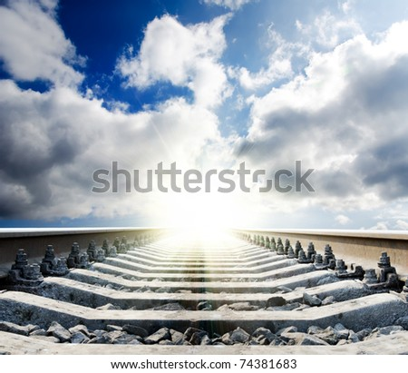 railway to sun under cloudy sky - stock photo