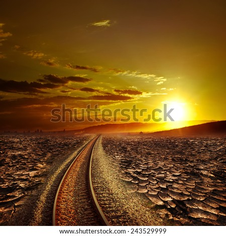 Railway track crossing drought cracked desert landscape under dramatic evening sunset sky. Global warming and travel concept - stock photo