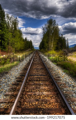 Railway track through mountain Wetlands, British Columbia, Canada in springtime - stock photo