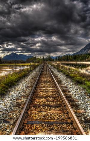Railway track through mountain Wetlands, British Columbia, Canada in springtime - stock photo