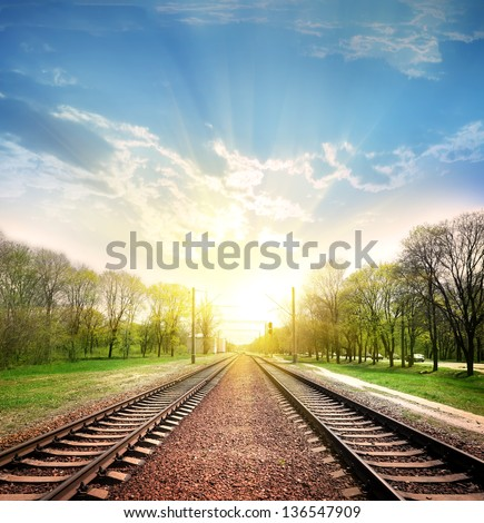 Railway tracks in a rural scene with nice pastel sunset - stock photo