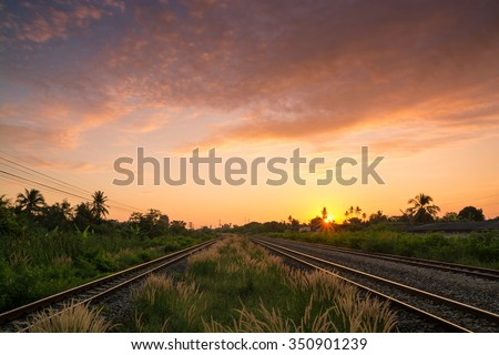 Railway tracks in a Rural Scene with Nice Sunrise and Grass Field
