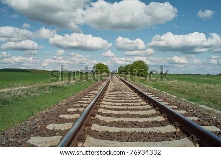 railway tracks on background of scenery - stock photo
