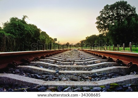 railway tracks with pale pastel sunset and frog point of view - stock photo