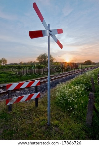 railway tracks with pastel sunset and traffic sign in a rural scene